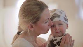 La mujer caucásica linda está deteniendo al bebé en manos y lo está besando encendido con la cara feliz almacen de metraje de vídeo