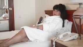 La mujer caucásica miente en una cama en un hotel en una albornoz blanca y controla la TV usando el teledirigido El concepto metrajes