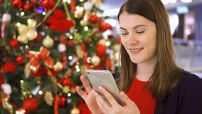 La mujer cerca adornó el árbol de navidad Bastante femenino usando el móvil que recibe enhorabuena en Año Nuevo metrajes