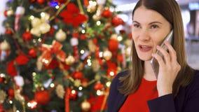La mujer cerca adornó el árbol de navidad Bastante femenino usando el móvil que recibe enhorabuena en Año Nuevo almacen de metraje de vídeo