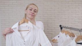La mujer cerca de la suspensión de ropa elige e intenta en la camisa blanca que mira en el espejo metrajes