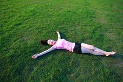 La mujer china asiática de la aptitud tiene un resto en la hierba en un parque imagenes de archivo