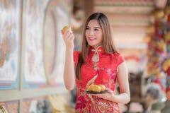 La mujer china asiática en chino tradicional que celebra el PA anaranjado Fotos de archivo libres de regalías