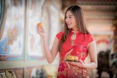 La mujer china asiática en chino tradicional que celebra el PA anaranjado Imagen de archivo libre de regalías