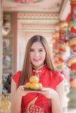La mujer china asiática en chino tradicional que celebra el PA anaranjado Imagenes de archivo