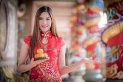 La mujer china asiática en chino tradicional que celebra el PA anaranjado Fotografía de archivo