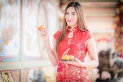 La mujer china asiática en chino tradicional que celebra el PA anaranjado Foto de archivo libre de regalías
