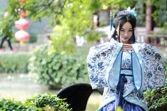 La mujer china asiática en el vestido azul y blanco tradicional de Hanfu, juego en un jardín famoso, se sienta en una silla de pi imagenes de archivo