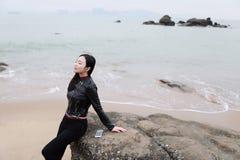 La mujer china asiática joven escucha la música se sienta en la roca de la playa de la arena fotografía de archivo libre de regalías