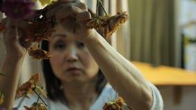 La mujer china cuelga exactamente hacia fuera la decoración floral en la pared almacen de metraje de vídeo