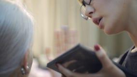 La mujer china en lentes elegantes aplica maquillaje en cara de bastante femenino metrajes