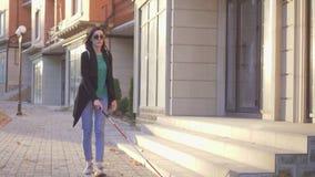 La mujer ciega joven con una mochila con un bastón pasa a través del rayo solar de la ciudad metrajes