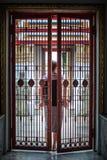 La mujer cierra la puerta de la puerta del hierro detrás de ella fotografía de archivo