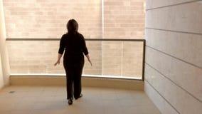 La mujer claustrofóbica se coloca en el balcón con una visión almacen de metraje de vídeo
