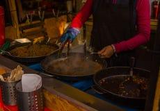 La mujer cocina la comida oriental deliciosa Imagen de archivo libre de regalías