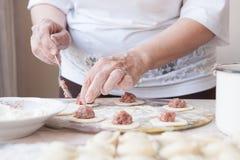 La mujer cocina las bolas de masa hervida en la cocina Foto de archivo libre de regalías