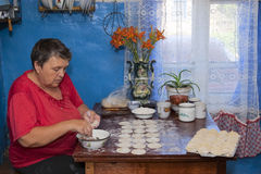 La mujer cocina las bolas de masa hervida en la cocina casera Imágenes de archivo libres de regalías