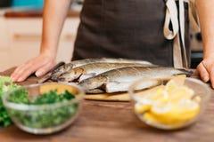 La mujer cocinará pescado el plato en cocina fotografía de archivo libre de regalías