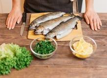La mujer cocinará pescados imagen de archivo