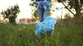 La mujer coge basura en un parque de la ciudad La responsabilidad social, iniciativa ambiental, ciudadanía, para el plástico almacen de video