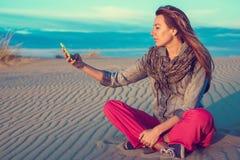 La mujer coge la conexión en su smartphone Foto de archivo libre de regalías