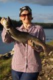 La mujer cogió un salmón hermoso grande Foto de archivo libre de regalías