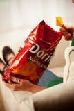 La mujer come a Chip From Bag Of Doritos, producido por la endecha C de Frito Imagen de archivo