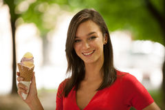 La mujer come el helado dulce al aire libre en parque Imagen de archivo