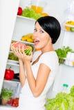 La mujer come el refrigerador cerca abierto de la sandía Imagen de archivo libre de regalías