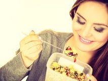 La mujer come la harina de avena con las frutas secas dieting foto de archivo