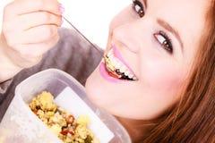La mujer come la harina de avena con las frutas secas dieting fotos de archivo