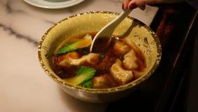 La mujer come la sopa china deliciosa de la bola de masa hervida almacen de metraje de vídeo