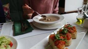 La mujer come la sopa de champiñones en un restaurante italiano almacen de video
