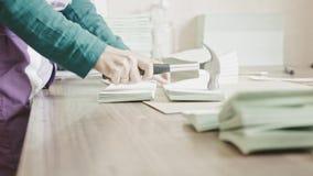 La mujer complementa las páginas del folleto con un martillo en la industria del polígrafo, trabajo manual almacen de video