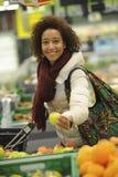 La mujer compra fruta y comida en supermercado Fotos de archivo