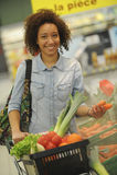La mujer compra fruta y comida en supermercado Imagen de archivo