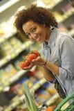 La mujer compra fruta y comida en supermercado Foto de archivo
