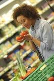 La mujer compra fruta y comida en supermercado Imagen de archivo libre de regalías