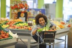 La mujer compra fruta y comida en supermercado Imágenes de archivo libres de regalías