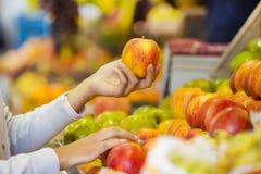 La mujer compra frutas y verduras en un mercado Imágenes de archivo libres de regalías