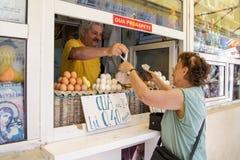 La mujer compra huevos en el mercado Fotos de archivo libres de regalías