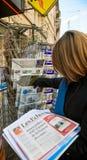 La mujer compra Les Echos, USA TODAY WEEKEND el periódico de un ne Imagen de archivo libre de regalías