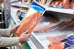 La mujer compra pescados rojos ligeramente salados en tienda Fotos de archivo