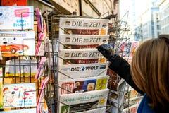 La mujer compra un periódico alemán de Zeit del dado de un quiosco Imagen de archivo libre de regalías