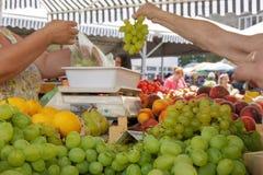 La mujer compra uvas en el mercado Imagen de archivo