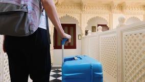 La mujer comprueba en el hotel y rueda la maleta a su sitio metrajes