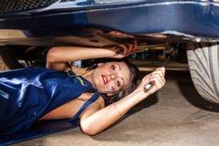 La mujer comprueba la suspensión del coche en servicio Imagen de archivo libre de regalías
