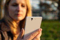 La mujer con apático hace frente y smartphone Imagenes de archivo