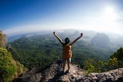 La mujer con backpacker disfruta de la opinión sobre el top de la montaña imagen de archivo