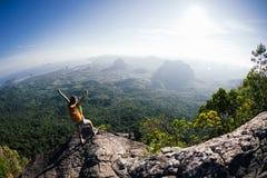La mujer con backpacker disfruta de la opinión sobre el top de la montaña imagen de archivo libre de regalías